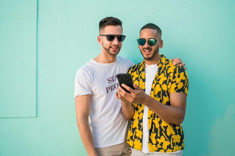 Young man using mobile phone by gay friend while standing against wall
