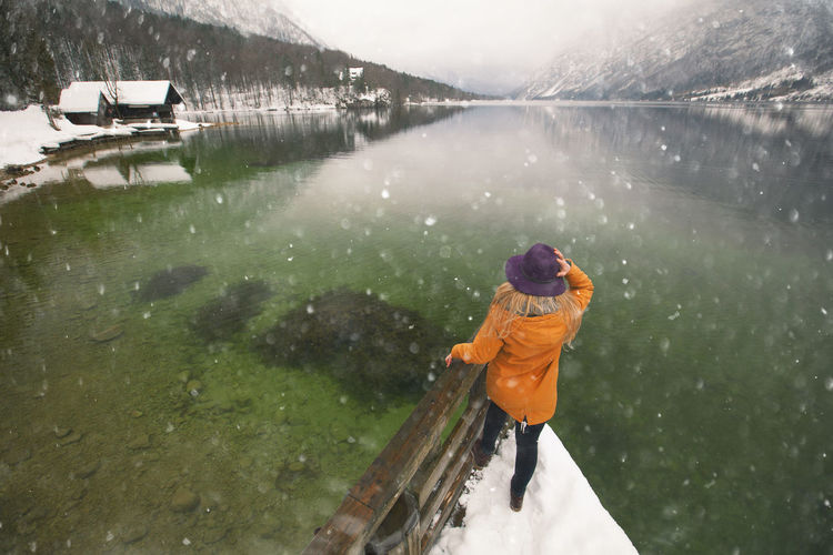 Rear view of woman on pier in lake during winter