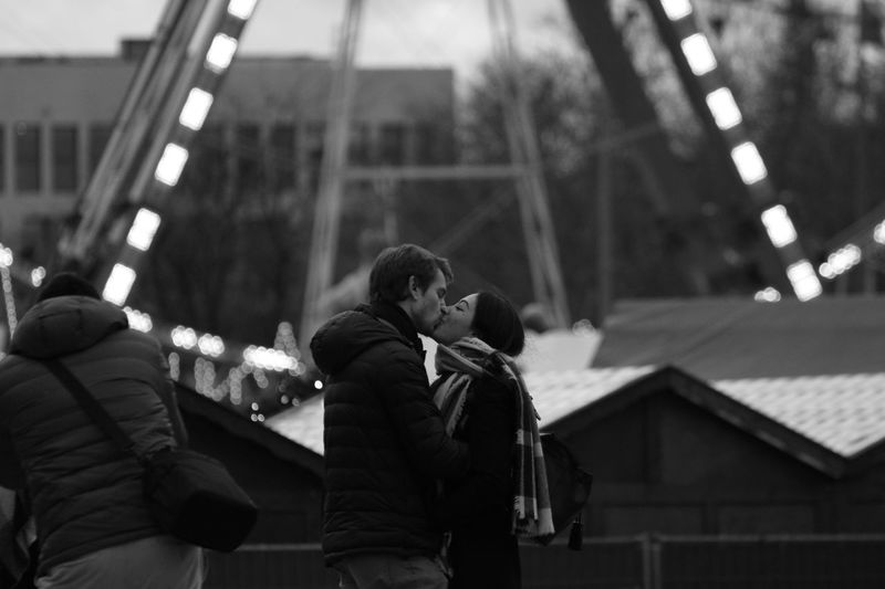 Side view of couple kissing while standing in city