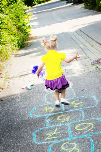 Girl on street playing hopscotch