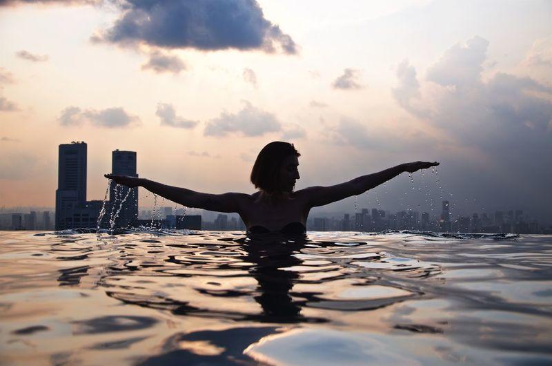 Full length of woman walking in swimming pool against sky