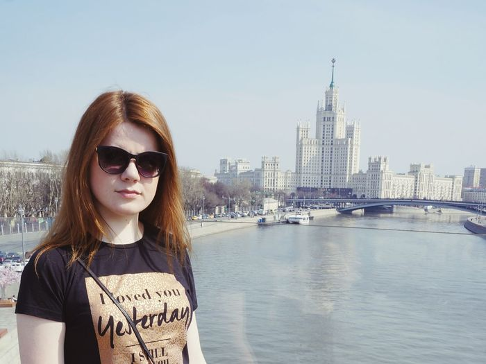 Portrait of young woman standing in city against sky
