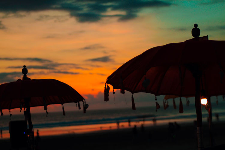 warm and cloudy Sunset Sky Umbrella Orange Color Silhouette Cloud - Sky Nature Beauty In Nature Parasol Protection Beach Land Water Beach Umbrella Horizon Over Water Tranquility