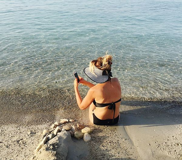 Rear view of woman sitting while using mobile phone on shore at beach