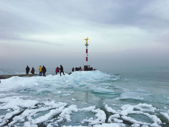 People by frozen sea against cloudy sky during winter