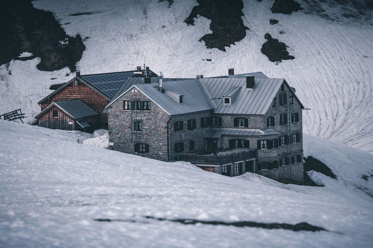 Snow covered houses by building in city