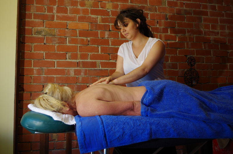 Young Massage Therapist Rubbing Back Of Woman