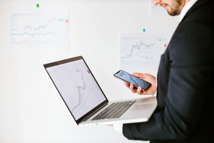 Midsection of businessman holding laptop and mobile phone at office