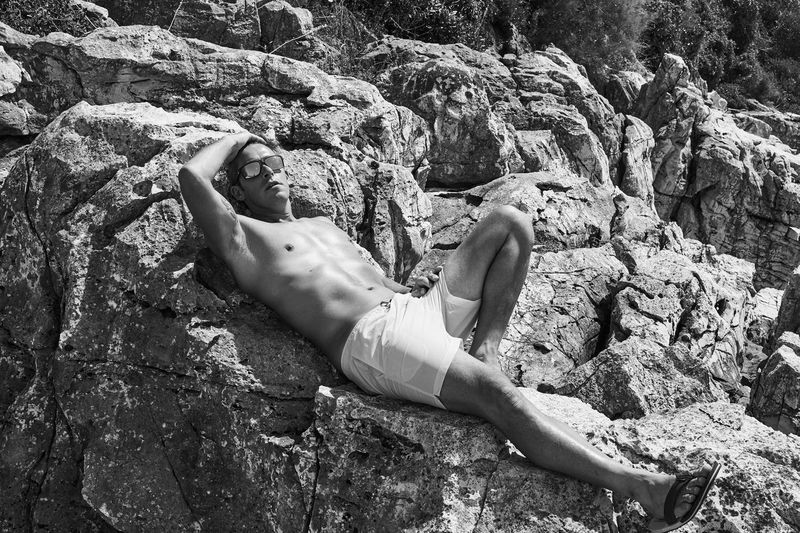 Portrait of shirtless mid adult man relaxing on rock during sunny day