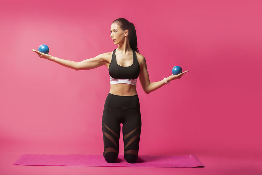 Long haired beautiful pilates or yoga athlete does a graceful pose with blue exercise balls while wearing a tight sports outfit against a pink background in a studio Body & Fitness Dance Exercising Silhouettes Stretching Legs Workout Flow Yoga Pose Abdominal Muscles Art Background Exercise Ball Fitness Outfit Long Hair Pilates Pilateslovers Pink Color Pose Pretty Girl Rubber Band Sports Clothing Studio Shot