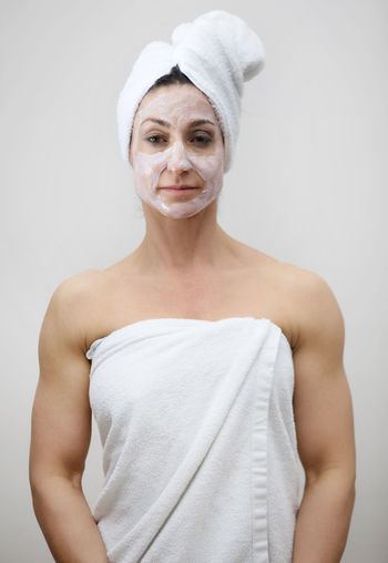 Portrait Of Woman With Face Mask Standing Against White Background