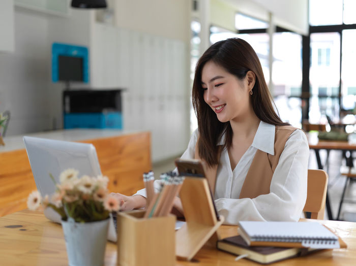 Smiling young businesswoman using laptop while sitting at cafe
