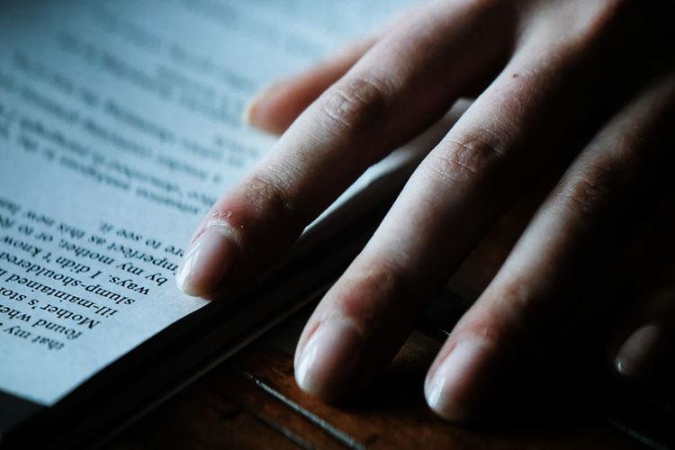 High angle view of hand on book