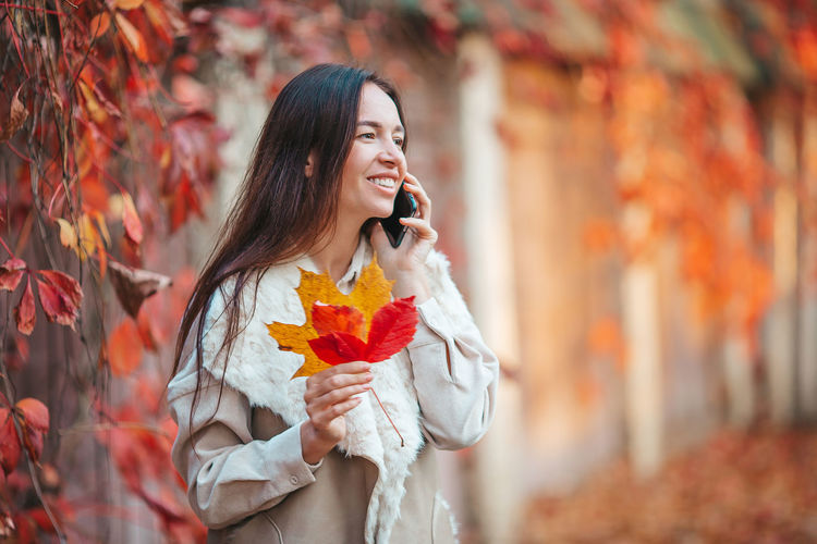 Young woman holding leaves during autumn