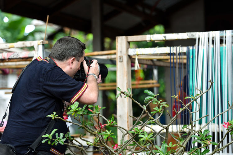 Young man photographing through railing