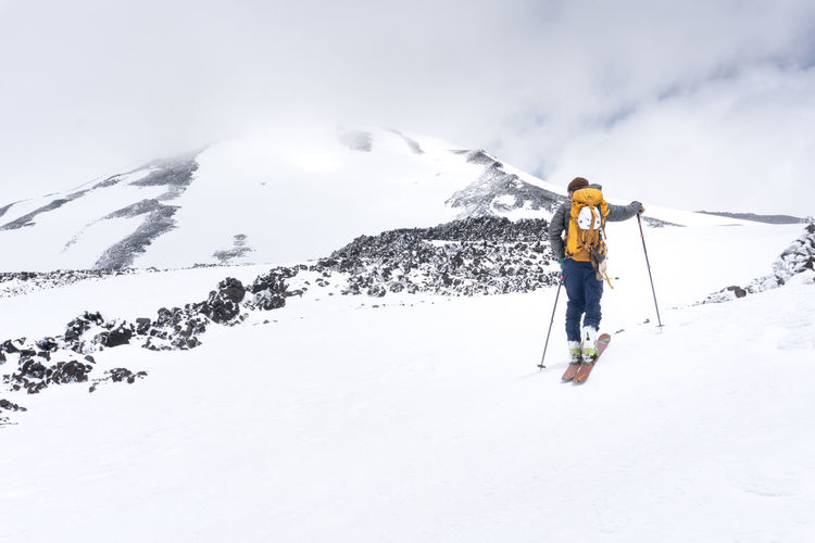 A skier looks at the summit of Mt. Adams Adventure Adventure Club Backpack Casual Clothing Cold Temperature Covering Day Enjoyment Full Length Landscape Leisure Activity Lifestyles Mountain Mt. Hood  Nature Outdoors Season  Sky Snow Vacations Warm Clothing Weather Winter