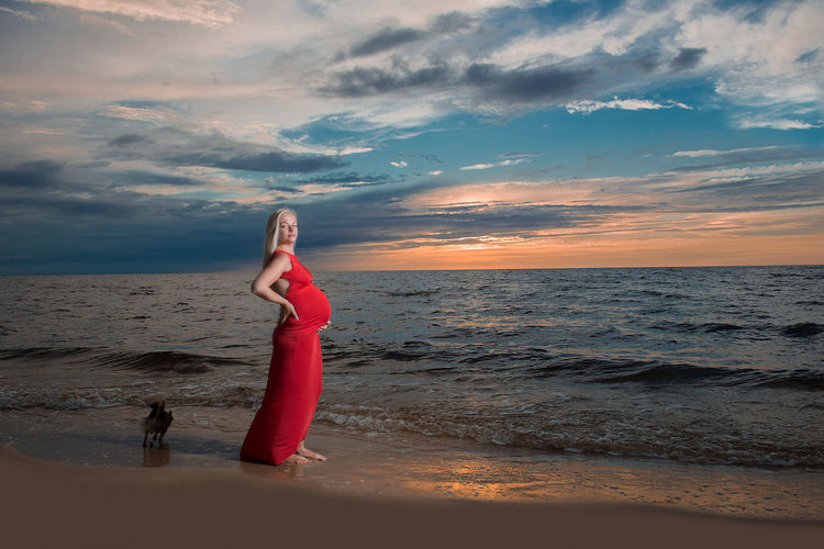 Portrait of pregnant woman standing on shore at beach against cloudy sky
