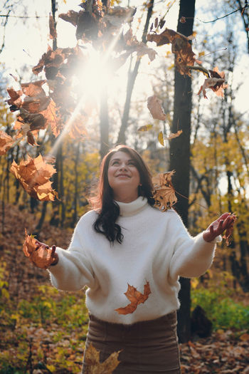 Full length of young woman standing in forest during autumn