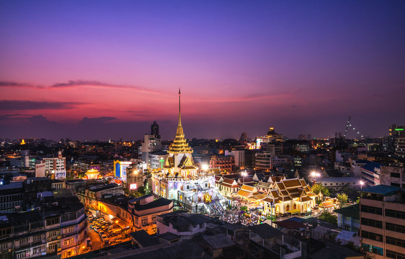 High angle view of illuminated stupa amidst buildings in city at night