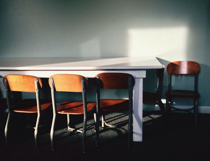 Empty chairs and tables by wall