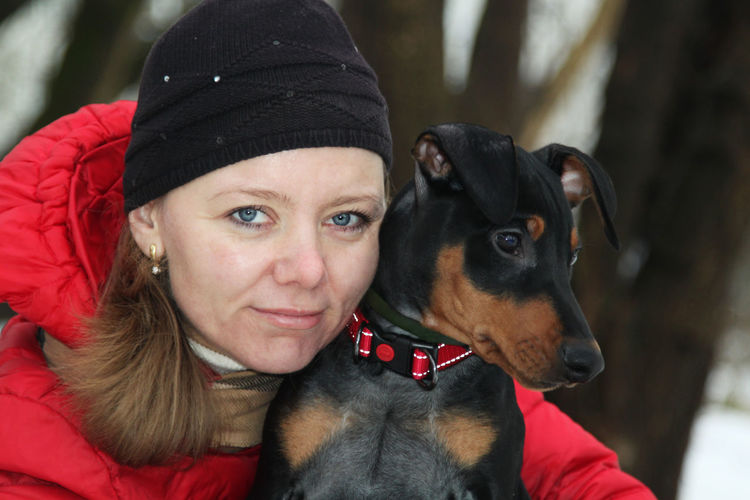Portrait of woman with dog during winter
