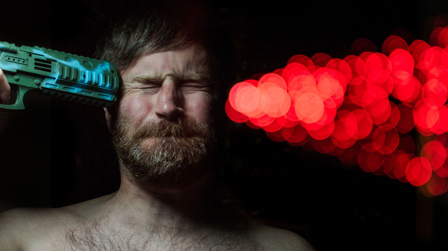 Optical Illusion Of Man Shooting Himself With Illuminated Red Light Against Black Background