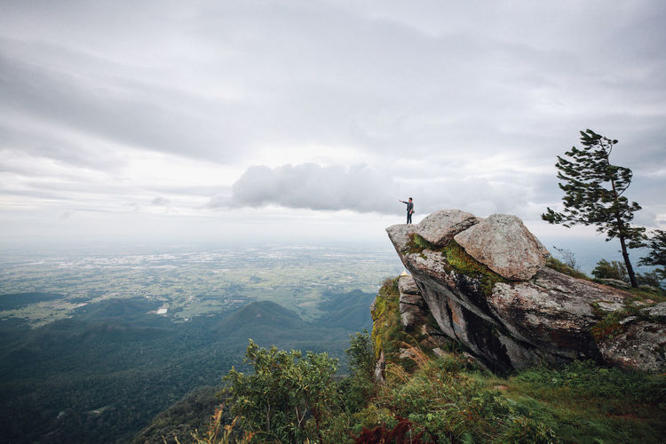 Hiker standing on cliff against cloudy sky during foggy weather