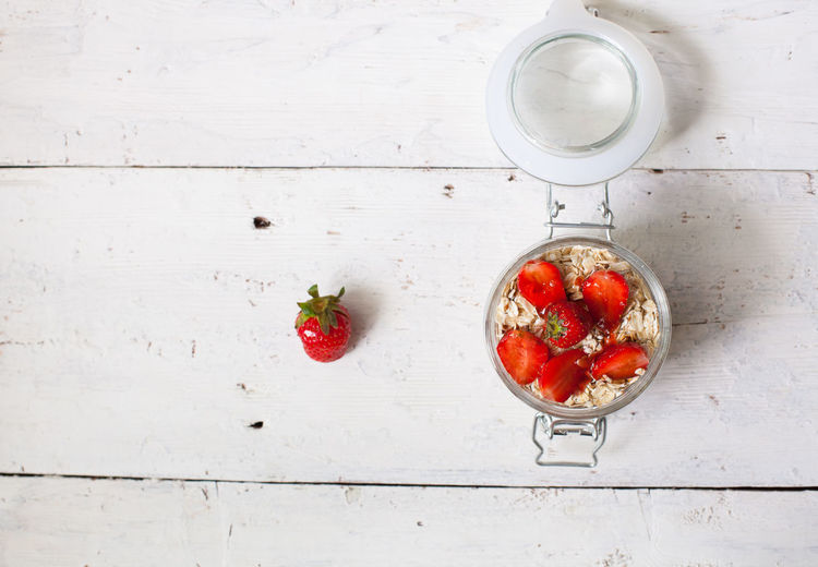 Full glass bowl of yogurt with fresh strawberries on the old white table Berry Fruit Close-up Cream Dessert Food Food And Drink Freshness Fruit Healthy Eating Indoors  No People Red Strawberry Studio Shot Wood - Material Yoghurt