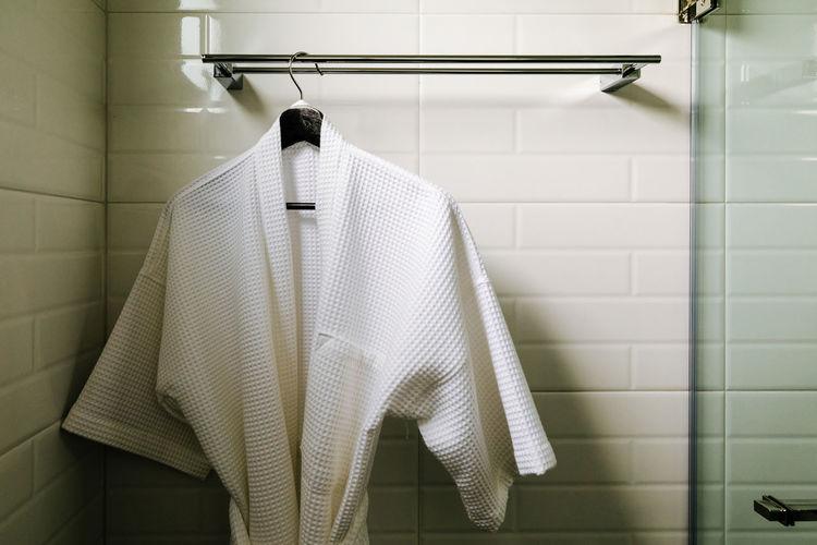 Bathrobe hanging against wall in bathroom