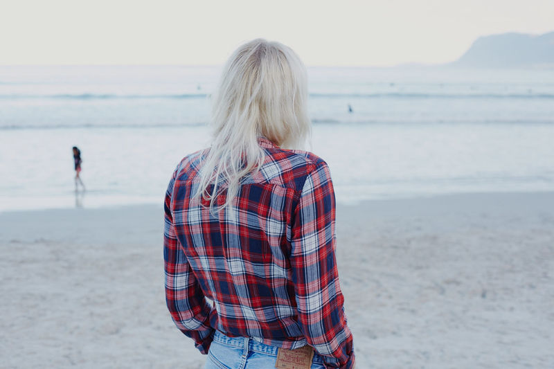 Beach Beauty In Nature Casual Clothing Day Focus On Foreground Horizon Over Water Leisure Activity Lifestyles Nature One Person Outdoors Real People Rear View Sand Scenics Sea Sky Standing Water Women Young Adult Young Women