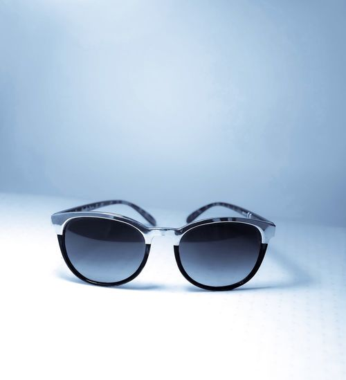 Close-up of sunglasses on table against blue background