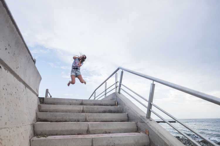 Full Length Of Woman Jumping On Staircase Against Sky