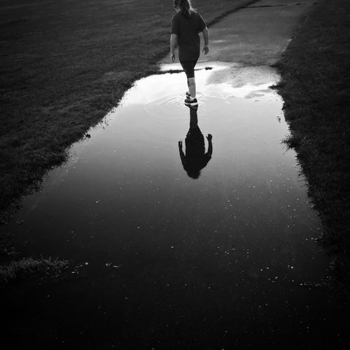 Reflections on youth Reflection Water Real People Lifestyles Puddle Wet Nature Walking Rainy Season Outdoors Day Road Rain Street Reflection City Silhouette Rain Nature International Women's Day 2019 The Art Of Street Photography