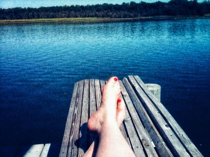 Low section of person relaxing on lake