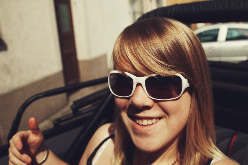 Portrait of smiling woman wearing sunglasses while sitting in car