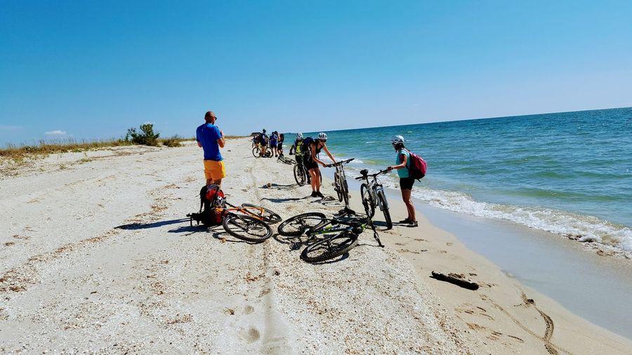 friendship Bike Bicycle Sun Teamwork Sea Beach Full Length Togetherness Clear Sky Sand Men Sunlight Shadow Friend Sand Dune Shining Mountain Bike Cycling