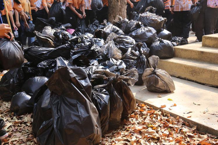 Heap of garbage bags on street in city