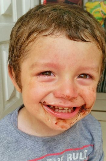 Portrait of playful boy with chocolate on face at home
