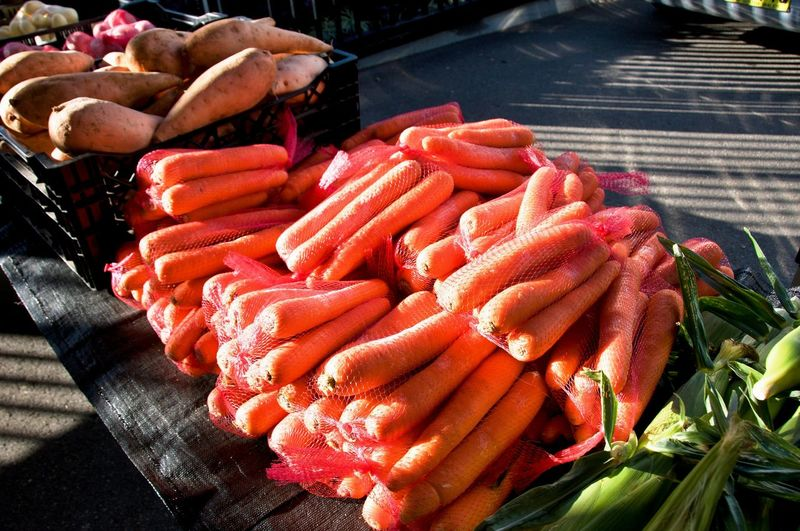 A table display of fresh nutritious vegetables at a farmer's market, includes, Carrots - (Daucus carota subsp. sativus), and Sweet Potato - (Ipomoea batatas) Market located in Gosford, New South Wales, Australia.