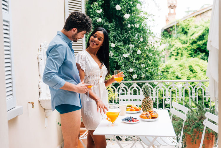 Smiling couple with food and drink on table standing in balcony