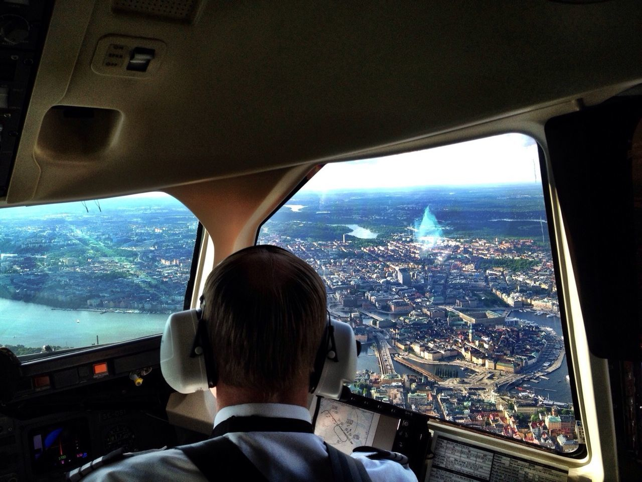 Rear view of pilot in airplane looking at city view through window