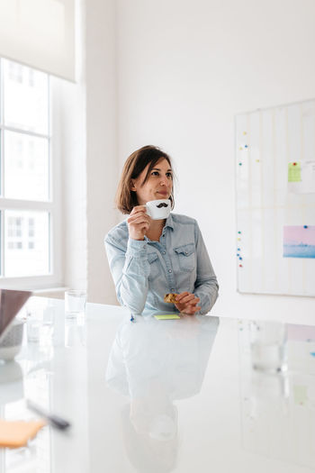 Businesswoman drinking coffee in meeting room at office