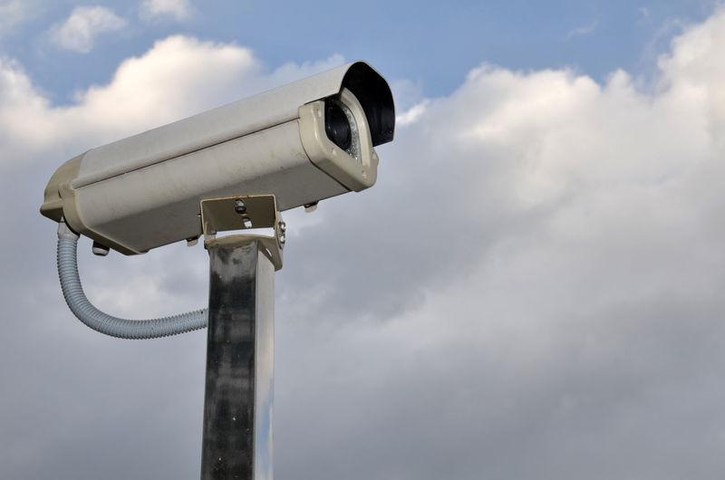 Low Angle View Of Security Camera Against Cloudy Sky
