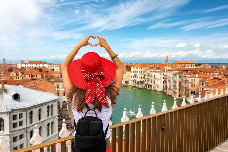 Traveler woman with red sunhat forms a heart with her hands over the skyline of Venice, Italy Architecture Building Exterior Sky One Person Water Women City Cloud - Sky Rear View Real People Lifestyles Leisure Activity Adult Cityscape Canal Outdoors Looking At View Young Women Young Adult Standing Heart Shape Hands Traveler Tourism Venice Italy Skyline Cityscape Veneto Arms Raised Summer Hat Woman