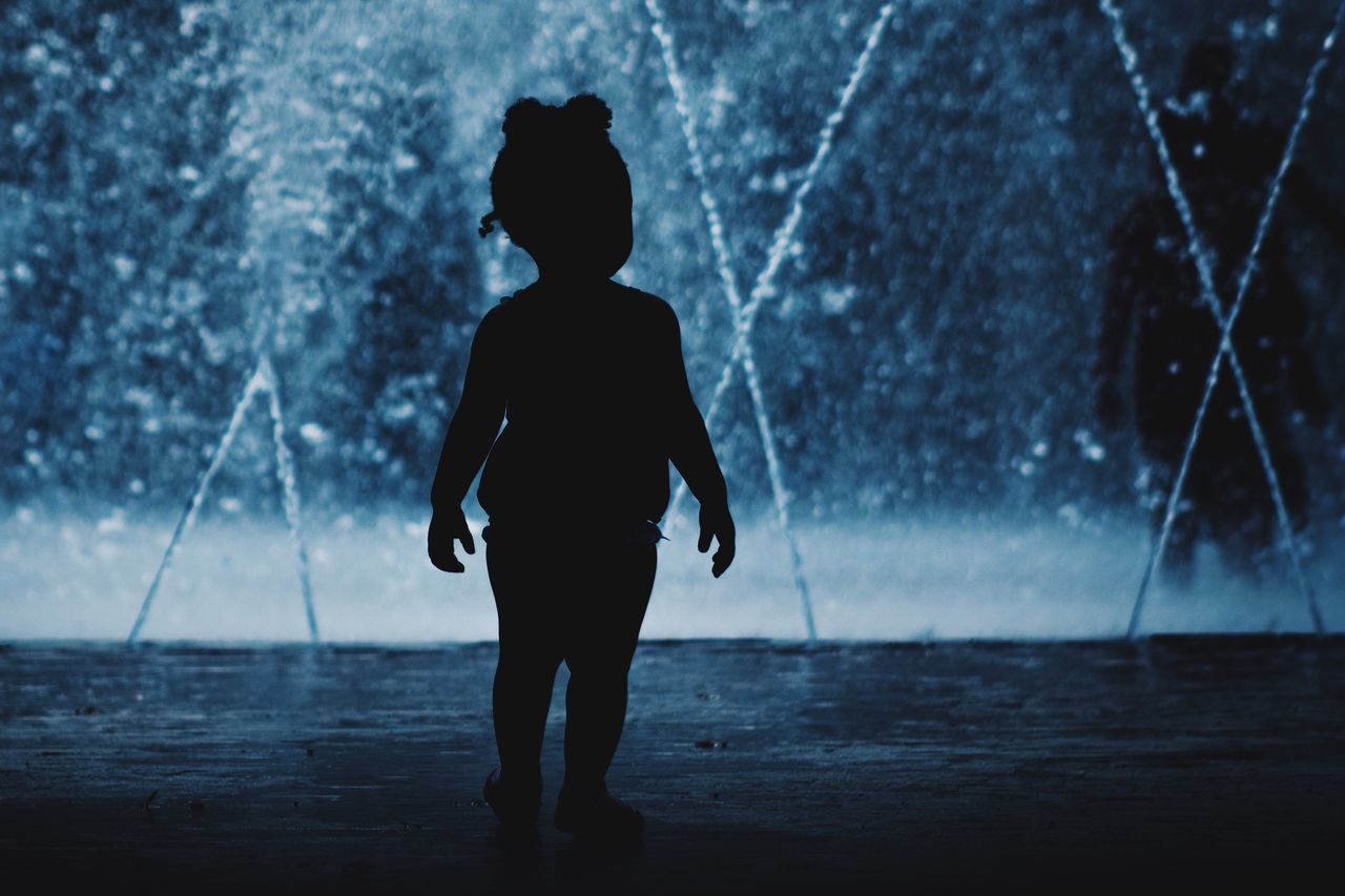 Silhouette girl against water fountain