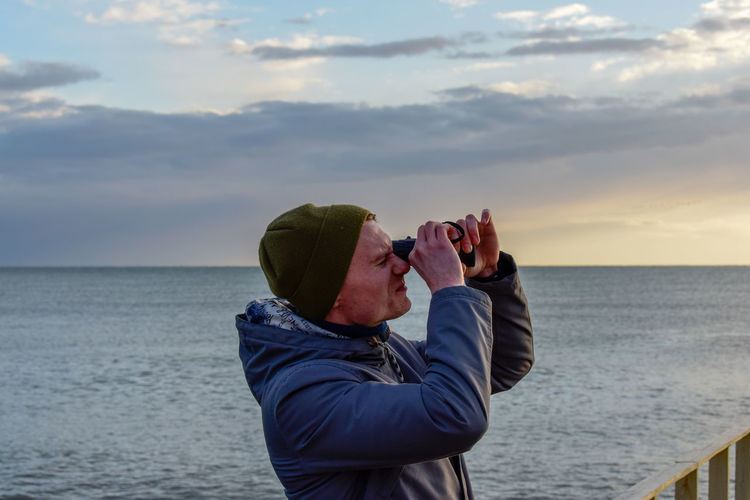 Profile view of young man looking through binoculars against sea during sunset