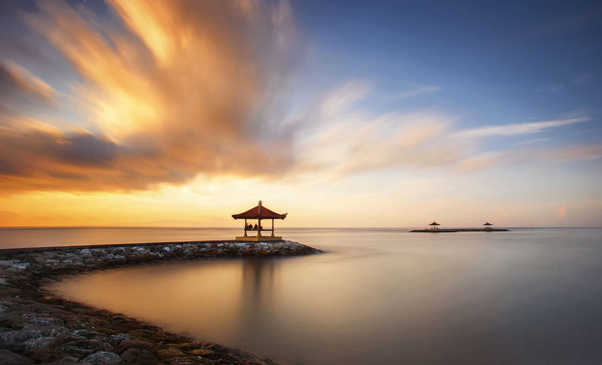 Beautiful gazebo or pagoda at the beach in Bali during sunrise or sunset with dramatic clouds and blue sky. Soft focus blur due to Slow Shutter speed. Dramatic Sky Gazebo Relaxing Architecture Beach Beauty In Nature Beauty In Nature Blue Sky Cloud - Sky Clouds And Sky Day Horizon Over Water Motion Nature No People Outdoors Reflection Scenics Sea Sky Soft Focus Sunset Tranquil Scene Tranquility Water