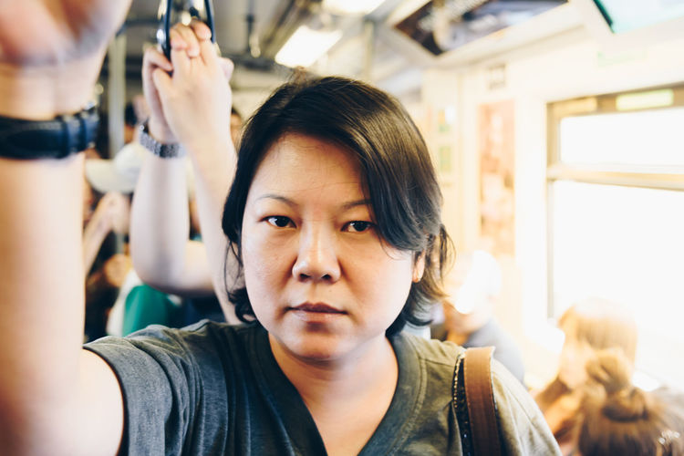 Close-up portrait of mature woman standing in train