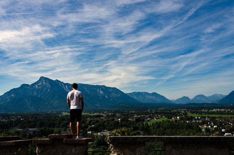 Rear view of man standing on retaining wall by landscape against sky