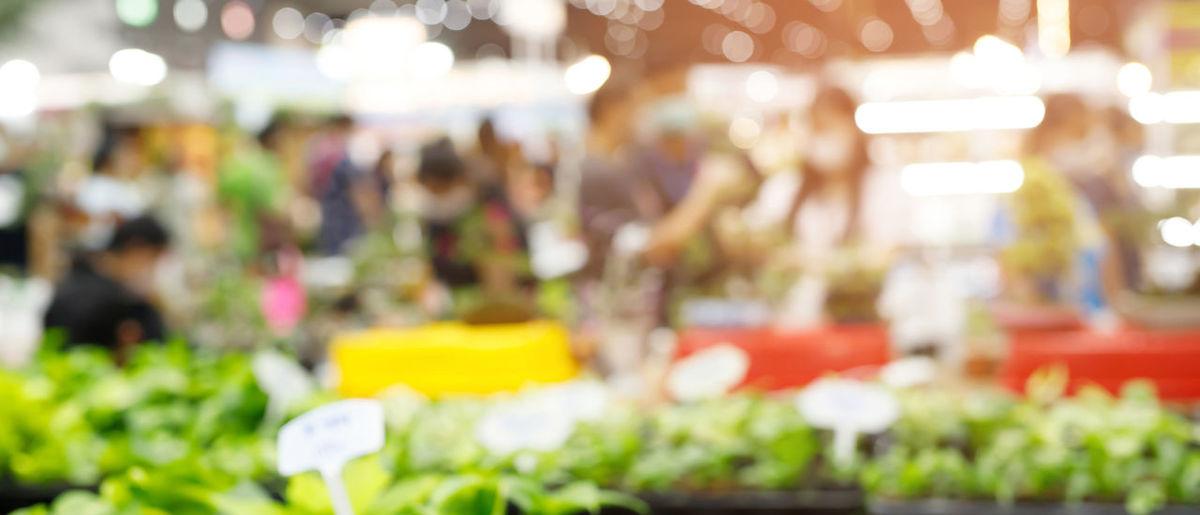 Defocused image of people at illuminated market stall